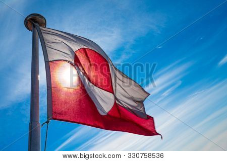 Greenland flag - Greenlandic flag against blue sky. Shot on Greenland on summer day. The National Flag of Greenland.