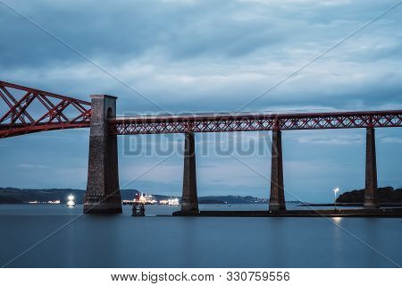 A Train Moving Over A Bridge Over A Sea. View Of Forth Rail Bridge, The Worlds Longest Cantilever Br