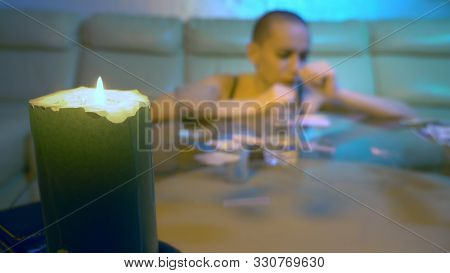The concept of night life. Glamorous bald woman sniffs a white powder through a twisted cupra. sitting at a glass table with alcohol and syringes in the living room, a candle in focus poster
