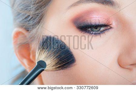 Makeup Artist Applying Makeup On Her Face Using Powder Brush