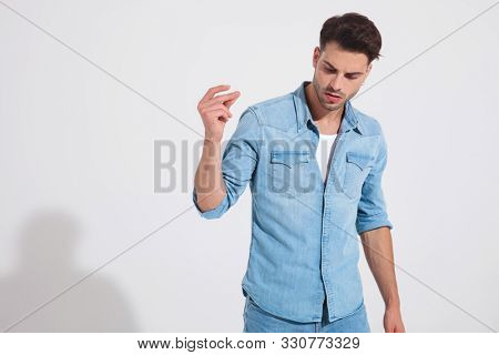 Tough fashion man snapping his fingers and looking away while wearing jeans and jacket, standing on light gray background