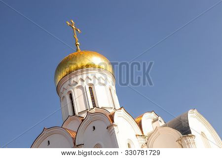 Top Part Of White Eastern Church With Sunlit Gilt Dome Against Clear Blue Sky