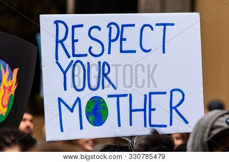 Protestors Are Viewed Close-up, Holding A Poster Saying Respect Your Mother With A Picture Of Planet