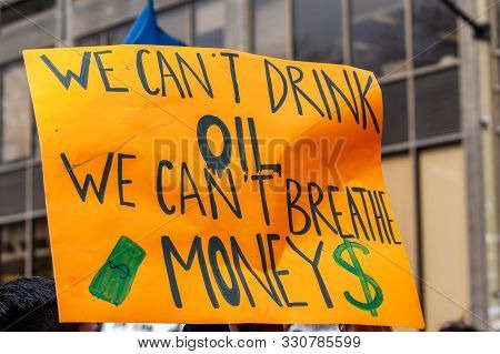 A Large Sign, Saying We Cant Drink Oil, We Cant Breathe Money, Is Viewed Close-up As Environmentalis