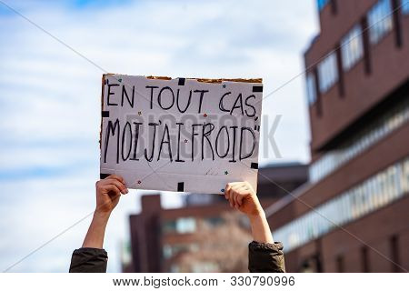A Closeup Shot Of A French Poster, Saying In Any Case, Im Cold, Held By An Ecological Activist As Pr
