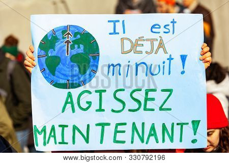 A French Poster Is Seen Close-up, Saying It Is Already Midnight Act Now, Held By An Environmentalist