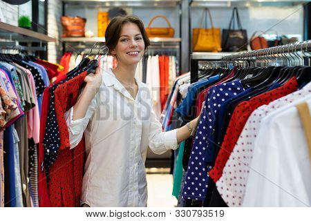 Young Smiling Woman Is Choosing Dress And Holding Polka-dot Dresses In Shop. Photo With Depth Of Fie