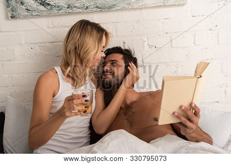 Happy Tender Couple With Rea Reading Book Together In Bed In The Morning