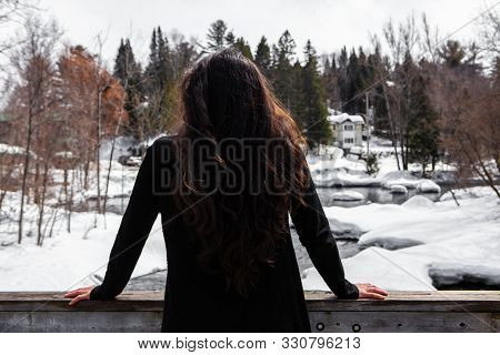 A Rear View Of A Lady With Long Hair Leaning Against A Wood Handrail, Contemplating The Heavy Snowfa