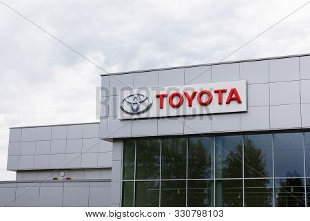 Minsk, Belarus - July 15, 2019: Toyota Logo And Signature On Gray Tiles Building With Dark Windows O
