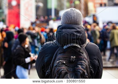 A Man Wearing A Backpack Is Viewed From Behind, As A Large Crowd Of Environmentalists Is Seen Blurry