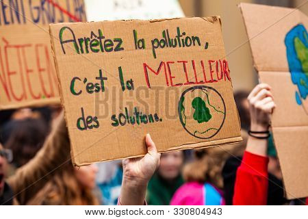 A Closeup View Of A French Placard Saying Stop The Pollution, Its The Best Solution, Is Held By An E