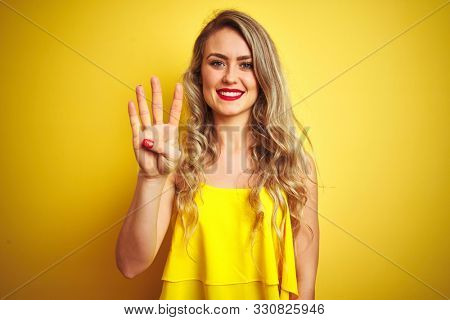 Young attactive woman wearing t-shirt standing over yellow isolated background showing and pointing up with fingers number four while smiling confident and happy.