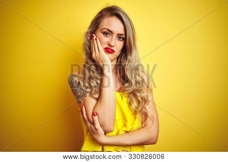 Young attactive woman wearing t-shirt standing over yellow isolated background thinking looking tired and bored with depression problems with crossed arms.
