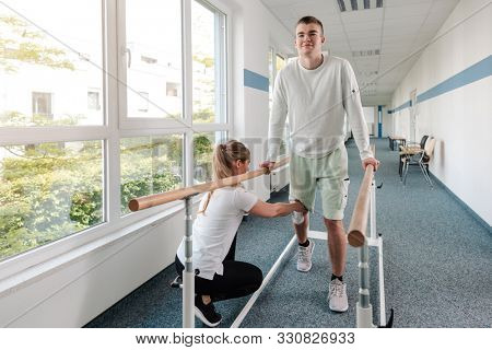 Young man in walking rehabilitation course after a sport injury on his knee
