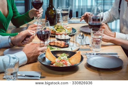 Plate of nice food in a fancy restaurant on table with people eating with guacamole in front