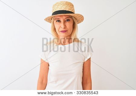 Middle age woman wearing casual t-shirt and hat standing over isolated white background with serious expression on face. Simple and natural looking at the camera.