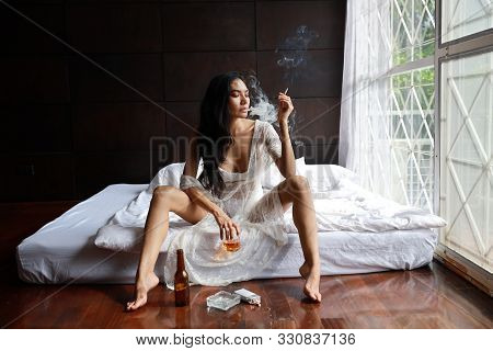 Drunken Asian Woman In White Lingerie, Drinking And Smoking While Holding Bottle Of Liquor Alcohol A