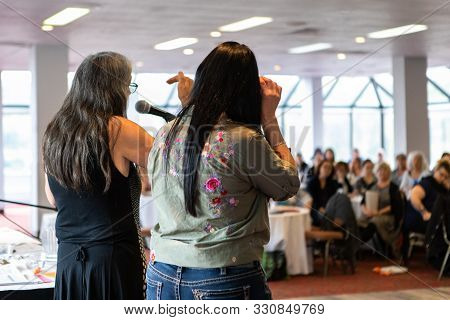 A Rear View Of Two Female Co-workers, Standing In Front Of A Room Full Of Work Colleagues And Speaki