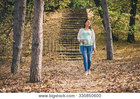 Happy Pregnant Woman Is Walking In Park.