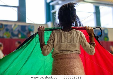 A Closeup And Rear View Of A Young Black Girl Holding A Rainbow Parachute During A Physical Educatio