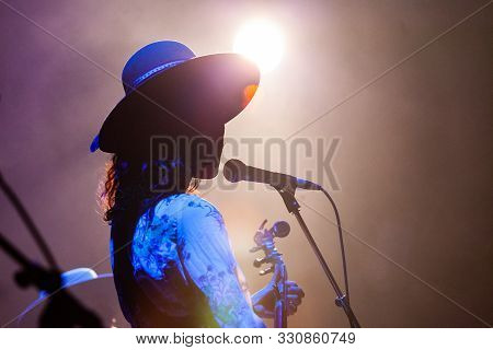 A Backlit View Of A Female Singer Performing On A Set With Bokeh Lens Flare. Atmosphere On Stage Dur