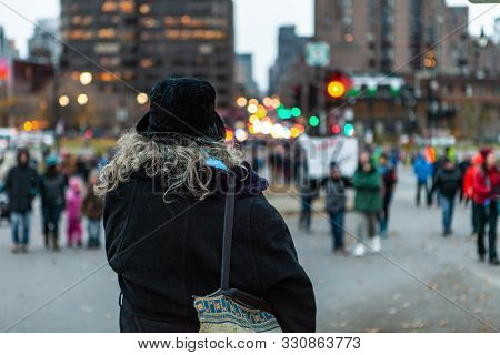 A Bystander Is Seen From The Back, Wearing A Black Hat And Jacket, Woman Stands Alone In The City Du