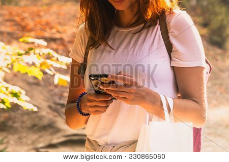 Woman Looking At Cellphone. Woman Looking At Cellphone While Walking In Park. Woman Reading Message
