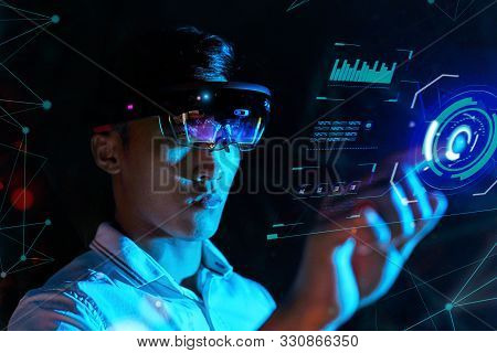 Business Man Try Vr Glasses Hololens In The Dark Room. Young Asian Boy Experience Ar With Glow Earth