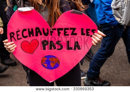 A Protestor Holds A French Sign Reading Warm The Heart, Not The Planet During A Crowded Demonstratio