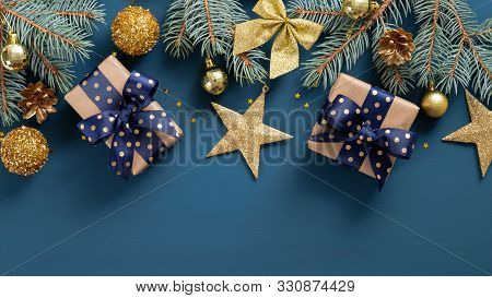 Wide Arch Shaped Christmas Border On Blue Background, Composed Of Xmas Tree Fir Branches And Ornamen