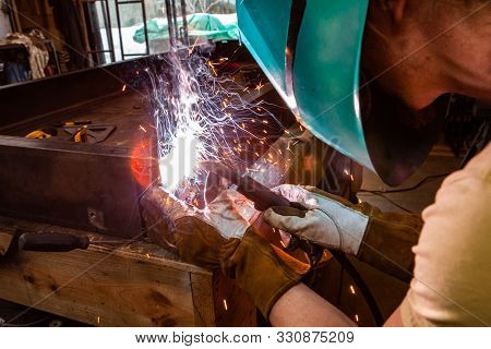 View From Behind A Tradesman Operating A Mig Welder. Protective Headgear And The Bright White Flash