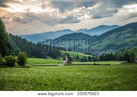 Dolomites, Italy - July, 2019: Green Alpine Valley With View Of Santa Maddalena Village Church, Val