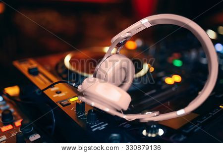 Closeup Pair Of Beige White Headphones For Dj.cd Mp4 Music Deejay Mixing Desk Music Party In Nightcl