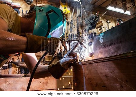 A Closeup View Of A Skilled Tradesman Operating A Metal Inert Gas Welder To Join The Corners Of Two
