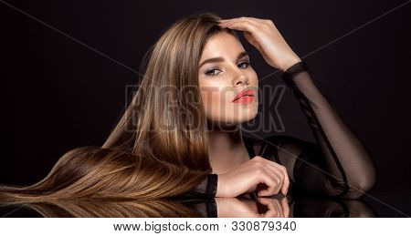 Woman with beauty long brown hair. Beautiful fashion model with long straight hair. Model with a smokey makeup. Pretty woman with orange color lipstick on lips.