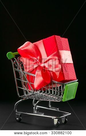 Present Gift Box In Festive Packaging With Satin Bow In The Shopping Basket. Delivery Of Gifts By Th