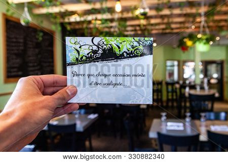 A Closeup View Of A French Card Held Inside A Modern Restaurant, Reading Because Every Occasion Dese