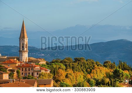 View of the beautiful Perugia medieval historic center and Umbria countryside at sunset with the iconic St Peter hexagonal belltower