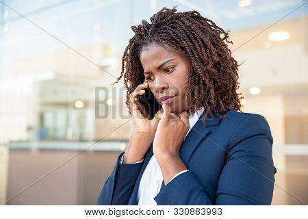 Frowning Concerned Manager Speaking On Cellphone Outside. Young African American Business Woman Stan