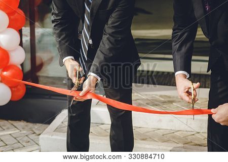 Businessman Cutting Red Ribbon With Pair Of Scissors. Two Man In A Classic Black Official Suit Cuts