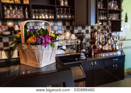 A Closeup View Of Colorful Flowers Arranged In A Small Wooden Basket Inside A Coffeeshop. Beautiful