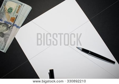 Blank Sheet Of Paper With A Stack Of Us Dollars In Top Right Corner And A Pen.