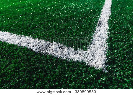 Green Football Field Closeup. White Marking Line On A Soccer Field. New Artificial Turf. Before The