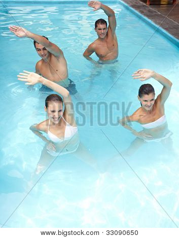 Happy group doing aqua fitness in swimming pool