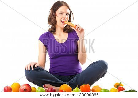 Healthy eating, happy woman with fruits and vegetables is eating a carrot