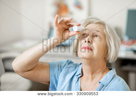 Senior Woman Dripping Some Medicine With Dropper On Her Eyes At The Ophthalmological Office. Concept