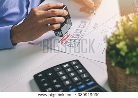 Businessman Accepting And Stamping Procurement Bill In Office