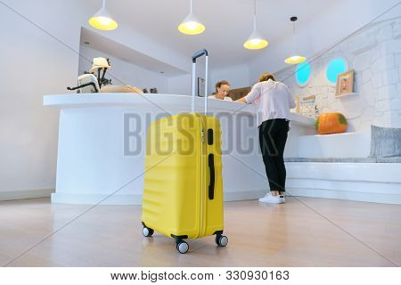 Concept Of Hotel Business, Travel, Tourism. Yellow Suitcase Near Reception Desk In Hotel Lobby