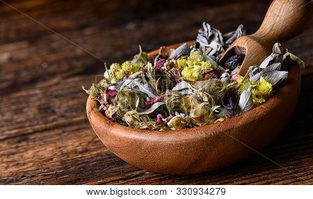 Healing Herbs From Various Medicinal Herbs And Flowers In Wooden Bowl With Scoope On The Rustic Tabl
